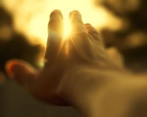 mano-sol-entre-dedos